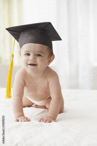 Hispanic baby wearing graduation cap