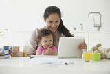 Hispanic woman holding daughter and using digital tablet