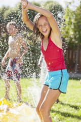 Caucasian girl playing in sprinkler