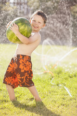 Caucasian boy carrying watermelon through sprinkler