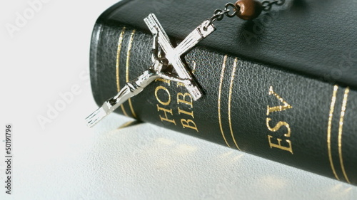 Rosary beads falling onto bible