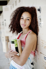 Mixed race woman leaning on school lockers