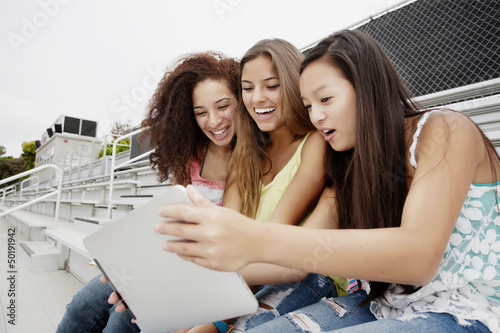 School friends sitting together on bleachers using digital tablet