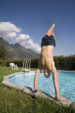 Man doing handstand on edge of swimming pool