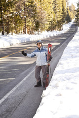 Hispanic man with skis hitchhiking