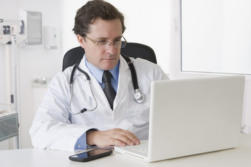 Caucasian doctor sitting at desk with laptop