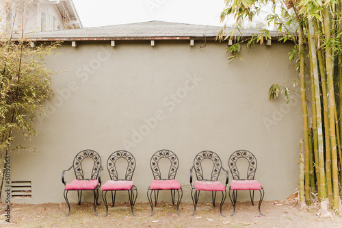 Chairs in a row against a wall