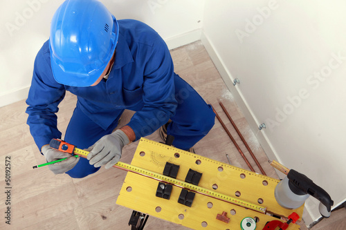Top-view of plumber measuring copper pipe