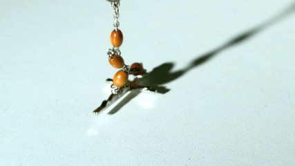 Rosary beads casting a shadow and then falling