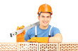 Male construction worker holding a bubble level and resting on a