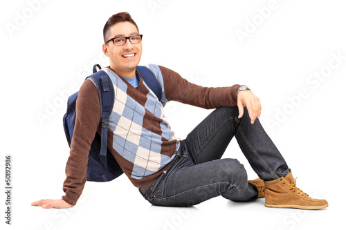 Smiling male student sitting on the floor
