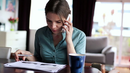 Young businesswoman with cellphone and documents working in home