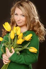 Attractive teenage girl with tulips in hands over black backgrou