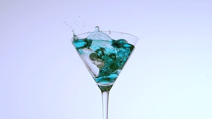 Ice falling into cocktail of blue liquid on white background