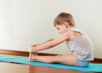 Little boy exercising and stretching in gym