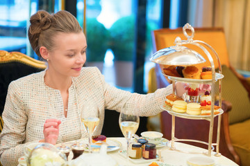 Beautiful young woman enjoying afternoon tea
