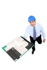 Businessman holding a model building