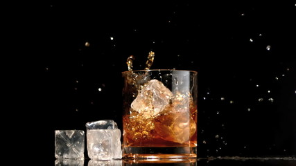 Ice cubes falling into glass of whiskey and ice
