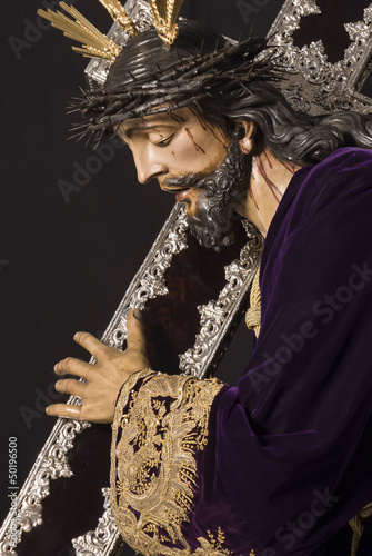 jesus with mahogany and silver cross on the shoulder