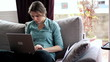 Young woman with laptop on sofa in home