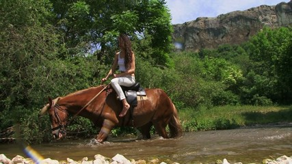 Horse falling in a river with horsewoman
