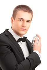 A portrait of a handsome male in black suit using parfume