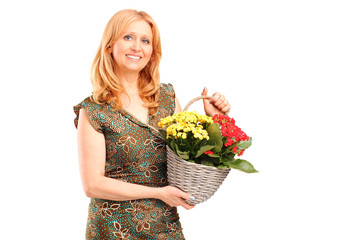 A smiling mature female holding flowers