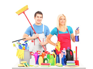 Male and female cleaners posing with cleaning supplies on a tabl