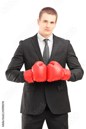 Handsome man in black suit with red boxing gloves posing