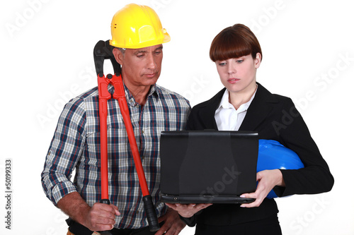 An architect and a foreman looking at a computer.
