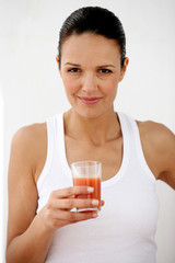 Brunette holding glass of tomato juice