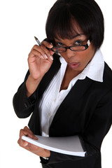 businesswoman looking upwards holding pen and notepad