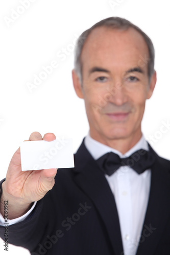 Grey haired waiter displaying business card