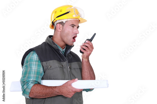 Tradesman yelling into a walkie-talkie