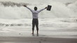 Freedom businessman screaming and raising hands while sea storm