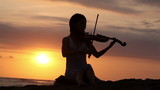 Violinist playing on violin romantic music while sunset