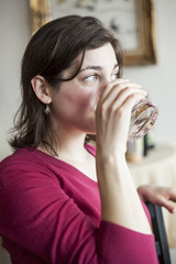 Beautiful Young Woman Drinks a Glass of Water