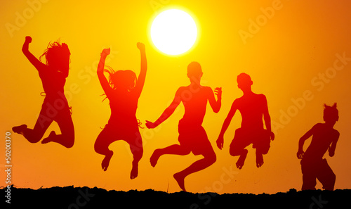 Silhouettes of happy teenagers jumping high in the air
