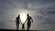 Silhouette of family walking together at summer