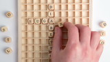 Hand spelling out diabetes message in wooden dice on grid