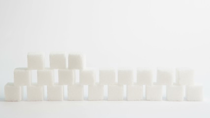 Sugar cubes forming with diabetes letter pieces balancing on top