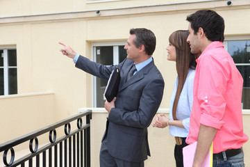 couple and realtor showing property