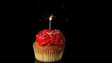 Sparkler burning on red birthday cupcake