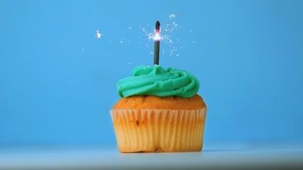 Sparkler burning on blue birthday cupcake