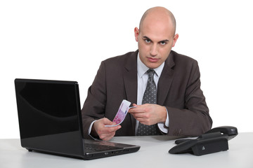 Businessman with a laptop and Euros