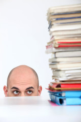 Man hiding behind a desk watching a stack of books