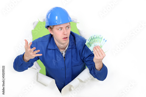 craftsman holding bills and looking surprised