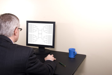 March Madness Business Man in Suit Looking at Bracket on Monitor
