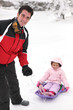 Father pulling daughter on sledge