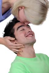 Woman kissing a man's forehead
